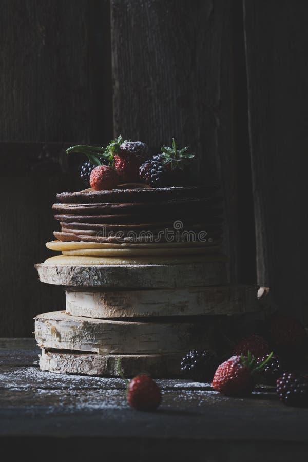 Prima colazione nel legno: pancake del cioccolato con le fragole, bl fotografie stock