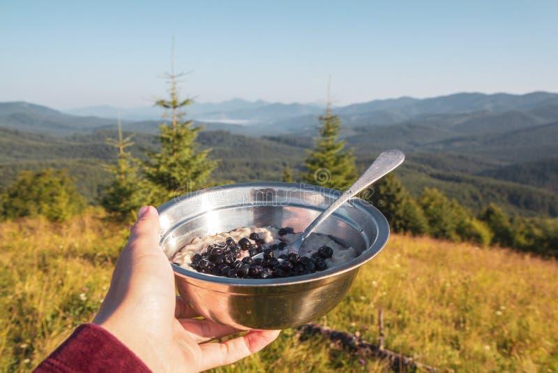 Prima colazione nell'aumento, una ciotola di porridge e bacche nella mano femminile sui precedenti del paesaggio della montagna d fotografie stock libere da diritti