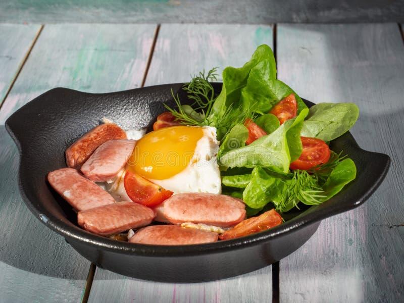 Prima colazione nutriente delle uova fritte con le salsiccie, i pomodori e la lattuga di foglia su una padella nera Servire su un immagine stock libera da diritti
