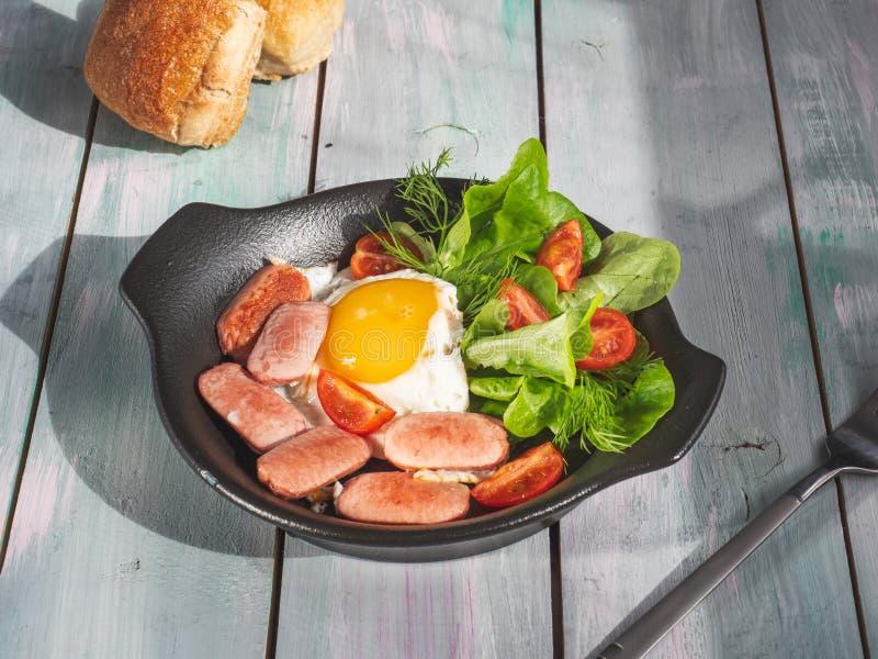 Prima colazione nutriente delle uova fritte con le salsiccie, i pomodori e la lattuga di foglia su una padella nera Servire su un fotografia stock libera da diritti