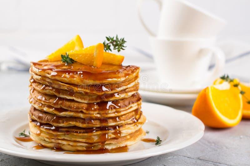 Prima colazione o brunch casalinga: i pancake stile americani sono servito con l'arancia ed hanno spruzzato lo sciroppo immagini stock libere da diritti