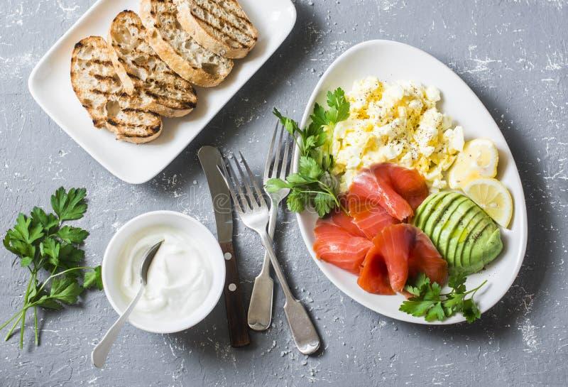 Prima colazione o spuntino equilibrata sana - salmone affumicato, insalata dell'uovo ed avocado Su un fondo grigio, vista superio immagini stock