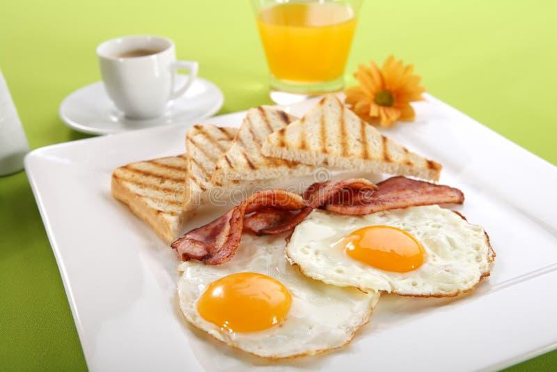 Prima colazione - pani tostati, uova, pancetta affumicata immagine stock
