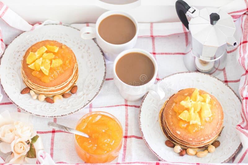 Prima colazione per 2 Vassoio con 2 piatti d'annata dei pancake con inceppamento arancio e dadi e 2 tazze di caffè macchiato Vist fotografia stock libera da diritti