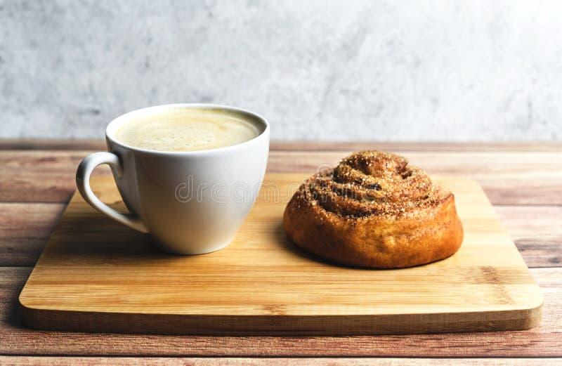 Prima colazione perfetta del panino e del caffè di cannella casalinghi sulla tavola di legno Stile rustico fotografie stock libere da diritti
