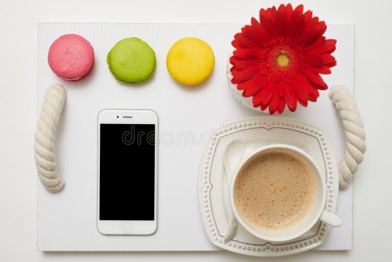 Prima colazione piacevole con caffè, i maccheroni ed il telefono cellulare sulla t fotografia stock