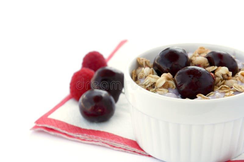 Prima colazione sana con i cereali, il yogurt, le ciliege ed i lamponi in ciotola bianca fotografia stock