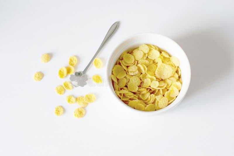 Prima colazione sana con i fiocchi di granturco ed il latte sopra fondo bianco fotografia stock