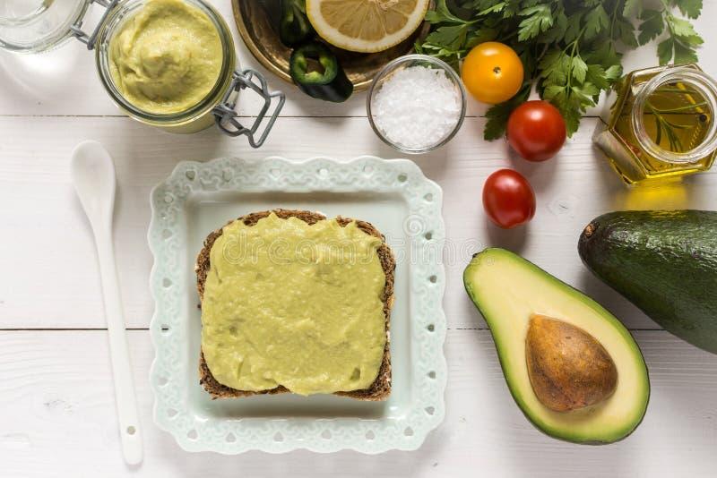 Prima colazione sana con il guacamole fresco di diffusione dell'avocado fotografia stock