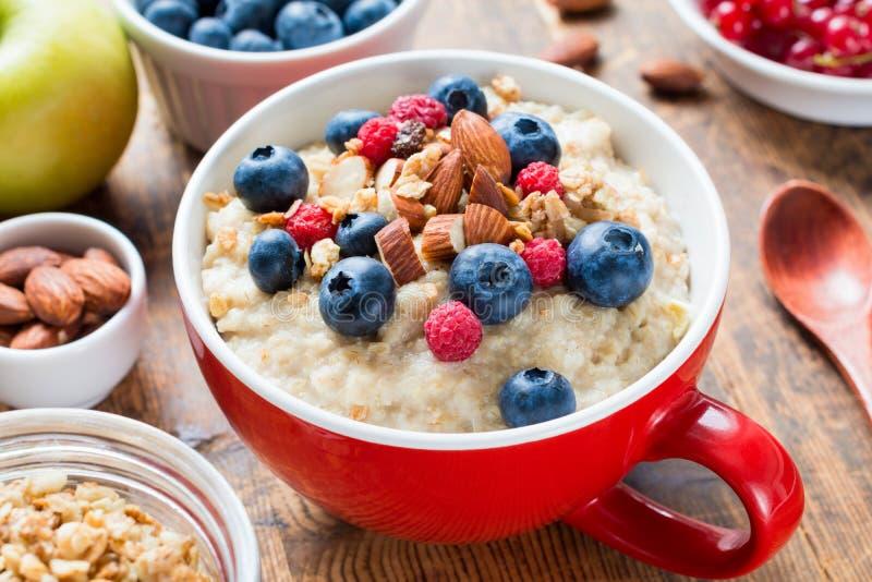 Prima colazione sana con il porridge della farina d'avena, le bacche fresche ed i dadi fotografia stock