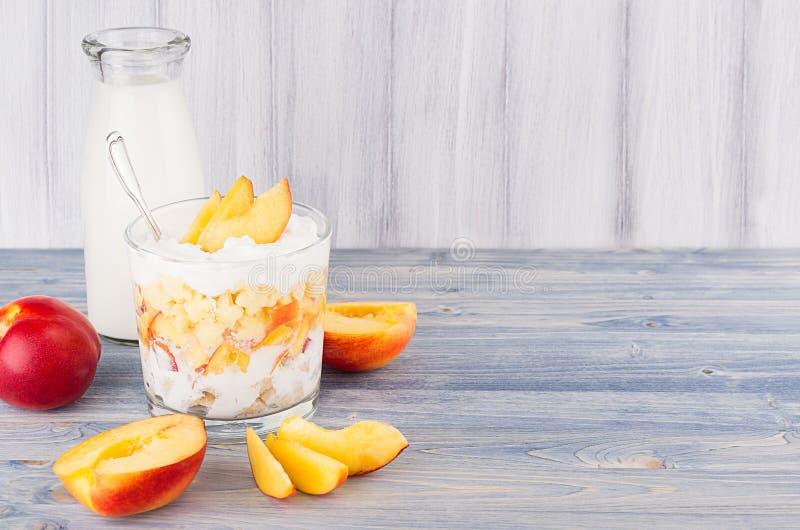 Prima colazione sana con la bottiglia per il latte dei fiocchi di mais, del pesca della fetta e sul bordo di legno bianco Confine fotografia stock