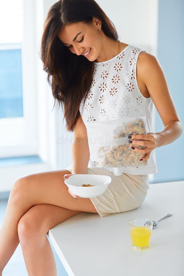 Prima colazione sana Donna che mette cereale in una ciotola immagini stock
