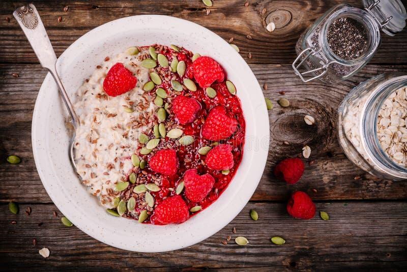 Prima colazione sana: farina d'avena con i lamponi, i semi di lino ed i semi di zucca freschi fotografia stock