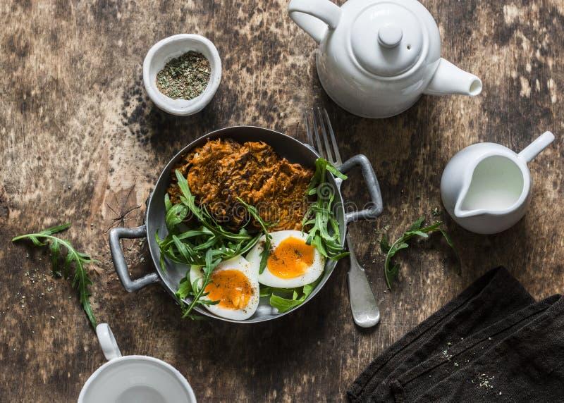 Prima colazione sana - frittelle della patata dolce, uovo sodo, insalata della rucola su fondo di legno fotografia stock libera da diritti