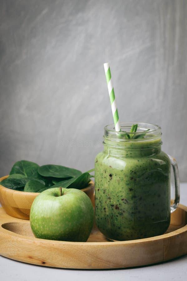 Prima colazione sana, frullato verde in un barattolo di vetro ed alcuni ingredienti - spinaci e mela Superfood, alimento della di fotografia stock