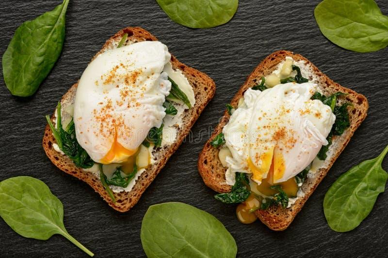 Prima colazione sana - panino con il formaggio, gli spinaci e l'uovo affogato della crema fotografia stock libera da diritti