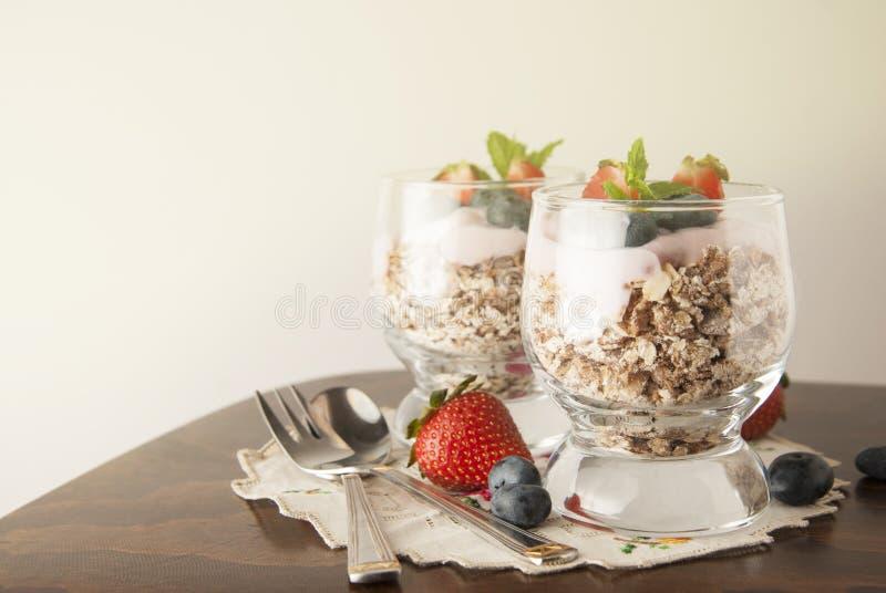 Prima colazione sana, pasto dell'avena con i frutti: bluebery, strawbery e min, parfait in due vetri su un fondo rustico Alimento fotografie stock libere da diritti