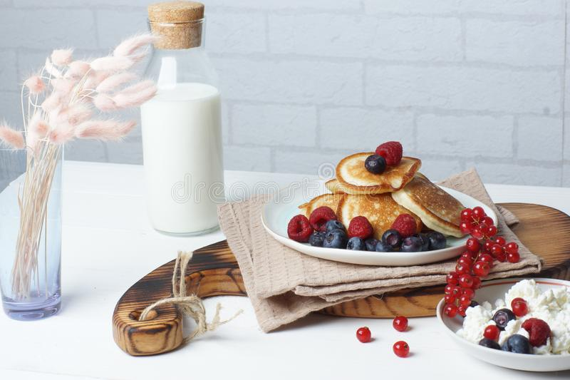 Prima colazione su una tavola bianca, sui pancake con le bacche, sulla ricotta fresca e su una bottiglia di latte immagini stock libere da diritti