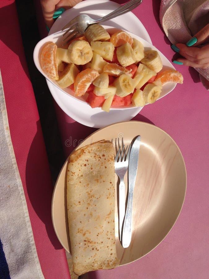 Prima colazione sulla spiaggia Pancake con frutta fotografie stock