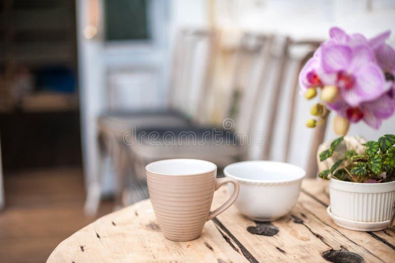 Prima colazione, tazze sulla tavola nel giardino Vecchia tavola d'annata strutturale nello stile rustico ed in orchidea Fiori con fotografia stock libera da diritti