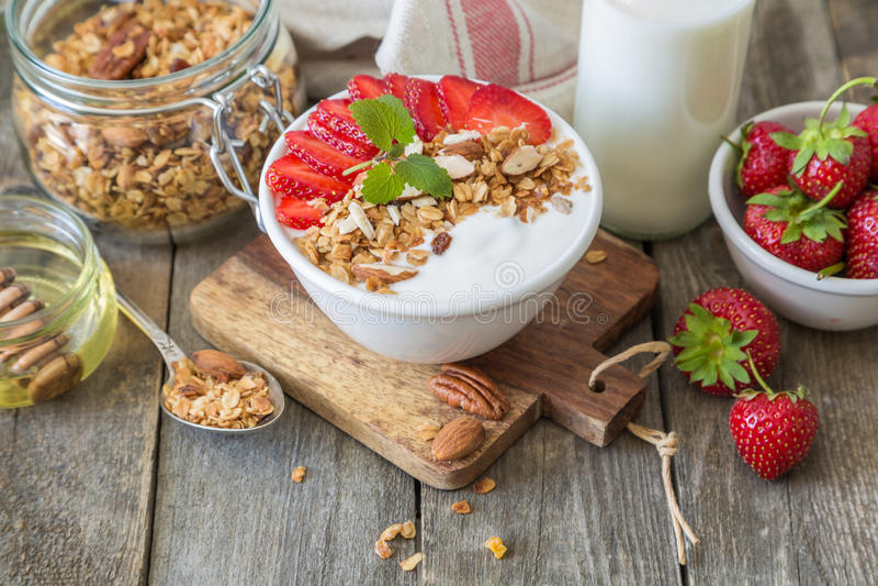 Prima colazione - yogurt con granola e straberries immagini stock libere da diritti