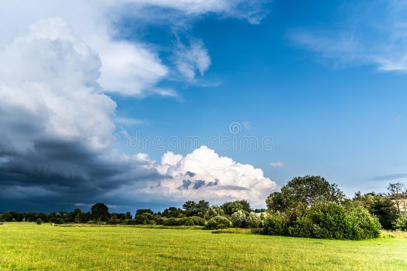 Prima della tempesta di estate Nuvole drammatiche che vengono nel paesaggio verde e soleggiato immagine stock