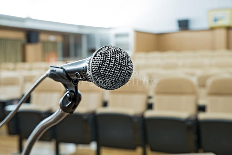 Prima di un congresso, i microfoni davanti alle presidenze vuote fotografie stock