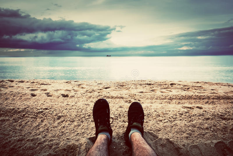 Prima prospettiva della persona delle gambe dell'uomo sulla spiaggia annata fotografia stock