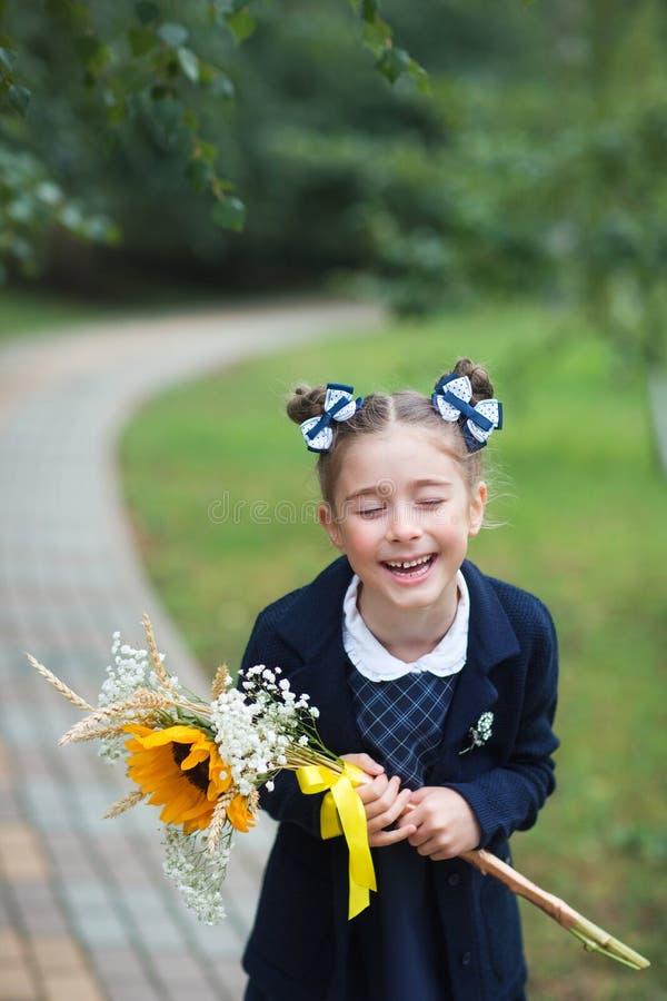 Prima ragazza del selezionatore con gli archi e mazzo nel primo giorno di scuola le risate dello studente fotografie stock libere da diritti