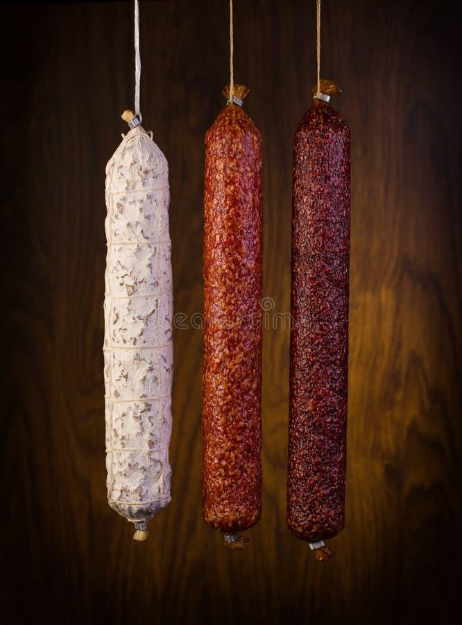 Prima salami som sorteras på en träbakgrund royaltyfri foto