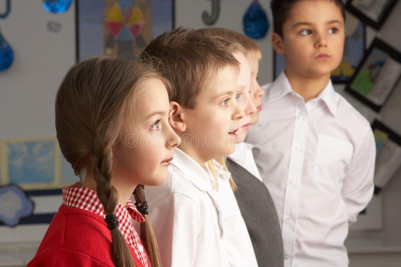 Primaire Schoolkinderen die zich in Klaslokaal bevinden stock afbeelding