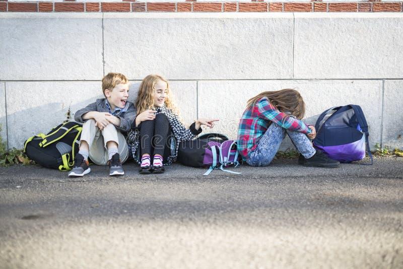 Primaire studenten buiten op school die zich droevig bevinden royalty-vrije stock afbeelding