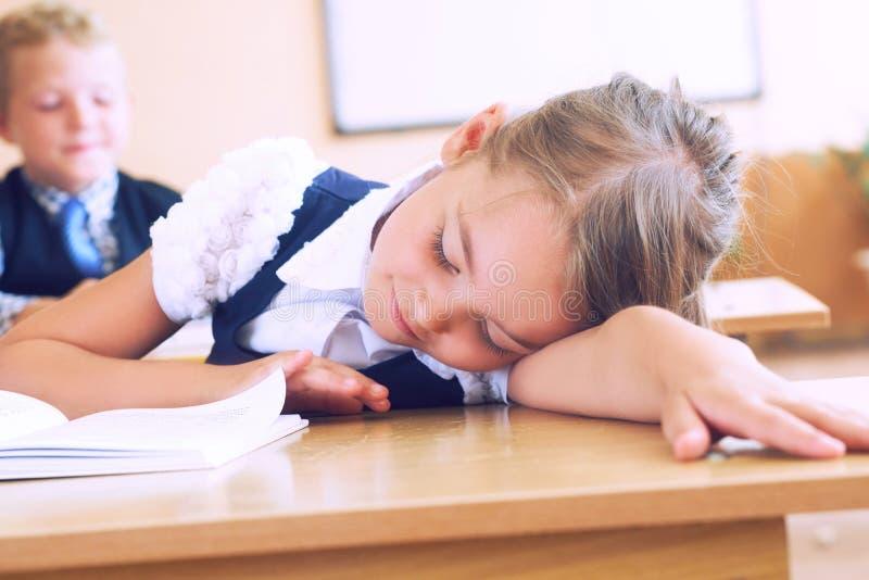 Primary little schoolgirl resting lying on desk. Primary Caucasian schoolgirl resting on desk royalty free stock image