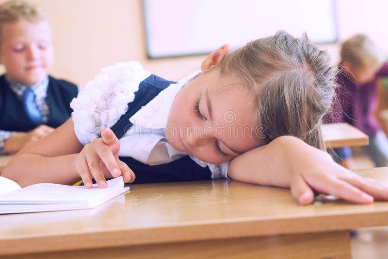 Primary little schoolgirl resting lying on desk. Primary Caucasian schoolgirl resting on desk stock photography