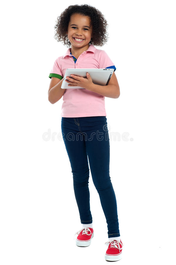 Primary child with a tablet pc smiling cheerfully royalty free stock photos