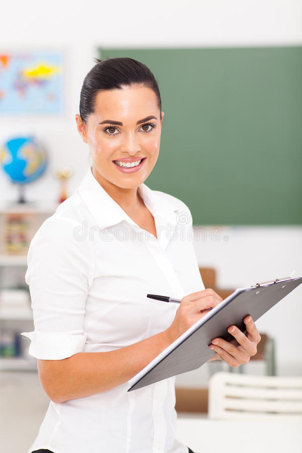 Primary educator. Pretty female primary educator writing on clipboard stock images