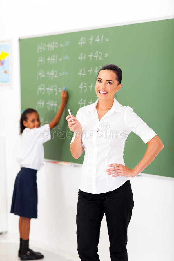 Primary maths teacher. Beautiful primary maths teacher in front of chalkboard in classroom stock photos
