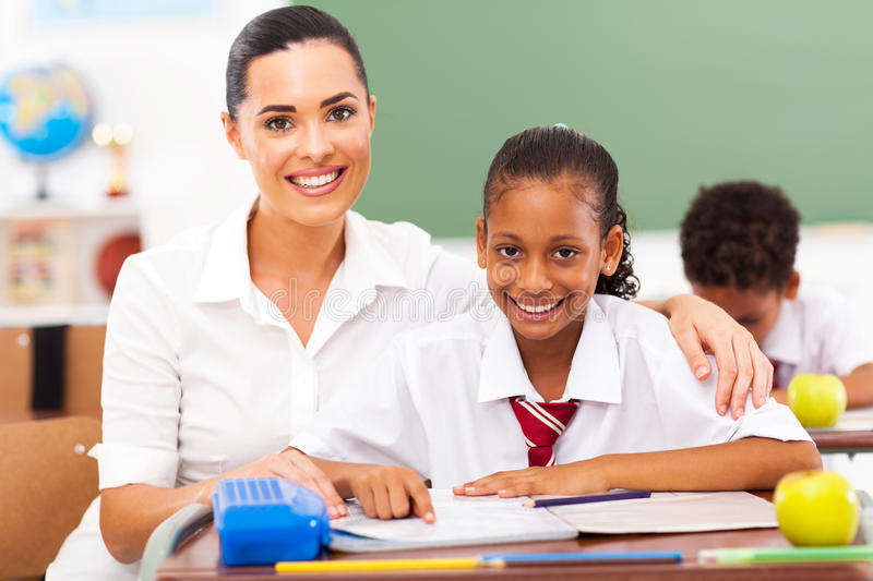 Primary school. Beautiful primary school teacher and students in classroom stock images