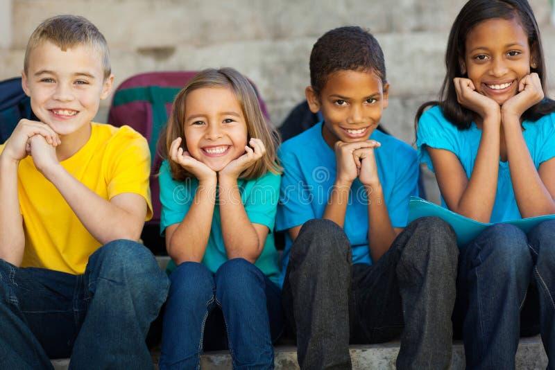 Primary school children. Cheerful primary school children sitting outdoors royalty free stock image