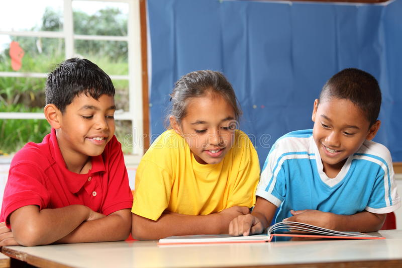 Primary school class reading and learning together stock photography