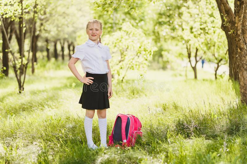 Primary school girl with backpack outdoors royalty free stock photos