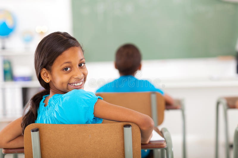 Primary school girl. Cute primary school girl in classroom looking back stock photography