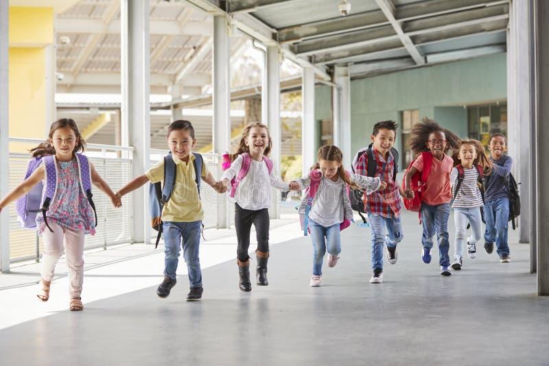 Primary school kids run holding hands in corridor, close up stock images
