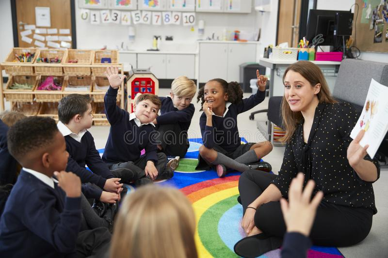 Primary school kids sitting on the floor in a classroom with their teacher, raising hands to answer a question, selective focus royalty free stock image