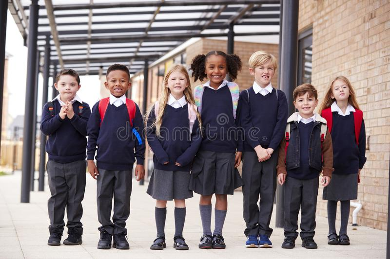 Primary school kids standing in a row on a walkway outside their school, smiling to camera, low angle stock images