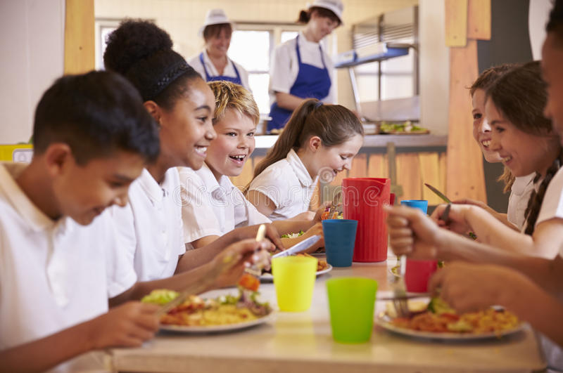 Primary school kids at a table in school cafeteria, close up stock images