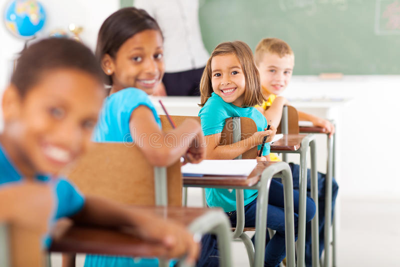 Primary school students. Group of primary school students in classroom looking back stock image