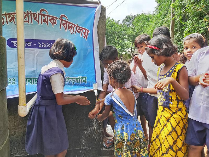 primary school students are washing their hand and their dishes before taking Mid-day meal in a primary school of West Bengal royalty free stock photography