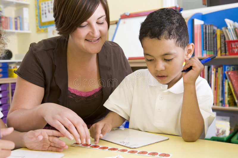 Primary school teacher helping boy learn numbers