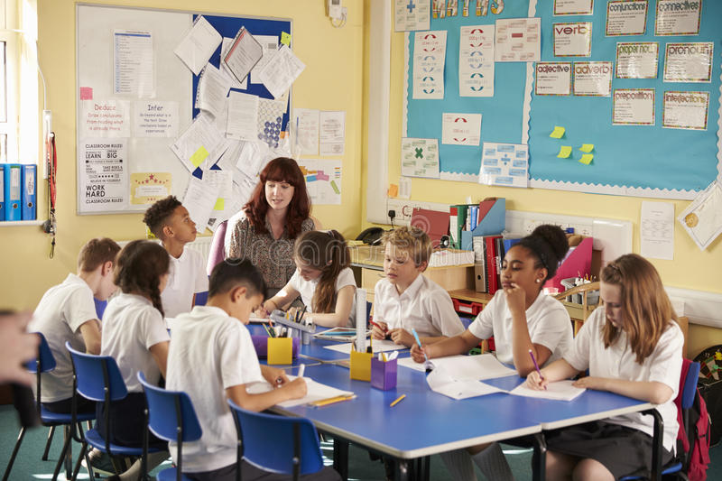 Primary school teacher with kids working on a class project royalty free stock photography